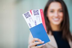 Image of European Woman Having Beautiful Brown Hair Smiling While Holding Passport and Air Tickets.  stock photography