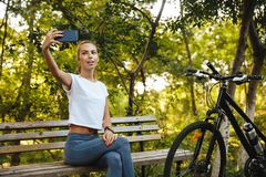 Image of european woman sitting on bench in park with bicycle, and taking selfie photo on cell phone stock photo