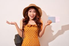 Image of excited brunette woman 20s wearing straw hat while holding passport with travel tickets isolated over beige background royalty free stock photography