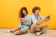 Image of excited couple or friends man and woman sitting on floor back to back and playing games on smartphones, isolated over ye. Image of excited couple or stock images