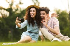 Image of man and woman 20s sitting on green grass in park and taking selfie on smartphone royalty free stock photos