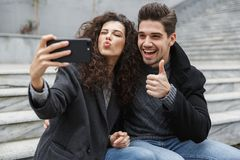 Image of excited couple man and woman 20s in warm clothes, taking selfie photo on cell phone while sitting on stairs outdoor royalty free stock photos