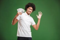 Excited emotional young african curly man showing money. stock photo