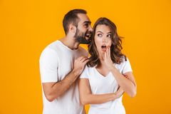 Image of excited man whispering secret or interesting gossip to woman in her ear, isolated over yellow background. Image of excited men whispering secret or stock images