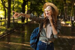 Excited shocked beautiful young happy woman walking outdoors with backpack pointing. stock image