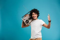 Excited young african curly man holding boombox. Image of excited young african curly man standing isolated over blue background holding boombox royalty free stock photography