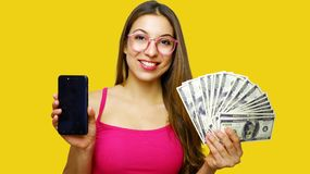 Image of excited young lady  over yellow background. Looking camera showing display of mobile phone holding money stock images