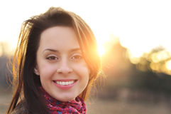 Image of a face beautiful female model in a colorful cotton scarf closeup on sunset background Stock Images