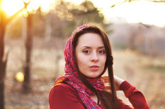 Image of a face beautiful female model in a colorful cotton scarf closeup on sunset background.  Stock Image