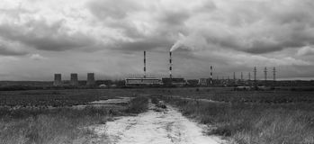 Image of factory in the middle of a meadow on a cloudy day Royalty Free Stock Photography