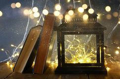image of fairy lights inside old lantern and antique books. Royalty Free Stock Images