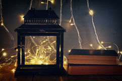 image of fairy lights inside old lantern and antique books. Royalty Free Stock Photography