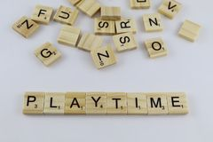 Scrabble game letters tiles on white background. This image features scrabble letters displayed to spell the word playtime, surrounded by a scattered assortment royalty free stock photos