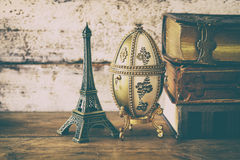 Image of feberge egg, decorative eiffel tower and vintage books. On wooden table. vintage filtered and toned stock photography