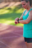 Image of a female athlete adjusting her heart rate monitor. A female athlete at a running track adjusts her heart rate monitor before a workout stock images
