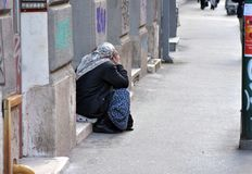 Image of female beggar sitting on the street side walk dressed as Muslim woman. royalty free stock photo