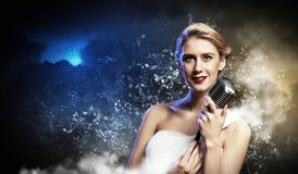 Female blonde singer. Image of female blonde singer holding microphone against smoke background Royalty Free Stock Images