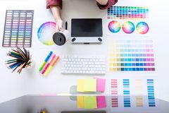 Image of female creative graphic designer working on color selection and drawing on graphics tablet at workplace, top view. Workspace royalty free stock photography