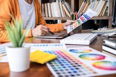 Image of female creative graphic designer working on color selection and drawing on graphics tablet at workplace with work tools. And accessories royalty free stock photos