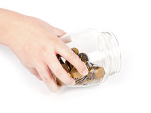 Image of female hand putting a coin into glass bottle Royalty Free Stock Photos
