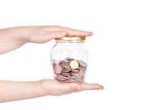 Image of female hand putting a coin into glass bottle Royalty Free Stock Photo
