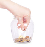 Image of female hand putting a coin into glass bottle Royalty Free Stock Images
