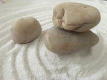 Zen stones on the raked sand wallpaper. Image of a few balancing zen stones on the takes white sand wallpaper royalty free stock photos
