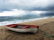 A fishing boat on the beach in Asprovalta, Greece. Image of a fishing boat standing on the sandy beach next to the sea in Greece Stock Photos
