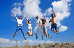 Image of five energetic people jumping at the beach stock photography