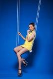 Image of flirtatious disco girl posing on swing Stock Photo