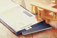 Image of flying ticket wooden airplane and passport over wooden table. retro filtered image royalty free stock photography