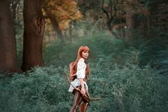 Image of a forest hunter, an attractive girl with long red hair in a white shirt and leather pants goes hunting, holds a royalty free stock photo