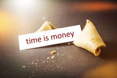 A fortune cookie with message time is money. An image of a fortune cookie with message time is money Royalty Free Stock Photography