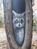 Image of fox painted on tree trunk. A lovely image of a fox drawn in white paint inside a bark split of a maple tree stock photo