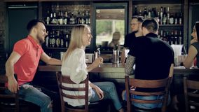 Image of friends sitting at bar counter while barman working on the other side of wooden table with window case in the. Back view of young friends relaxing in stock video