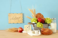 image of fruits, bread and cheese in the tin basket over wooden table. Stock Image