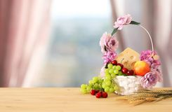 Image of fruits and cheese in decorative basket with flowers ove. R wooden table. Symbols of jewish holiday - Shavuot Royalty Free Stock Images