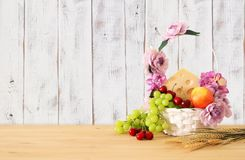Image of fruits and cheese in decorative basket with flowers ove. R wooden table. Symbols of jewish holiday - Shavuot Royalty Free Stock Photos