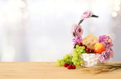 Image of fruits and cheese in decorative basket with flowers over wooden table. Symbols of jewish holiday - Shavuot. Image of fruits and cheese in decorative Stock Images