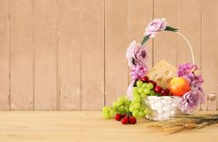 Image of fruits and cheese in decorative basket with flowers over wooden table. Symbols of jewish holiday - Shavuot. Image of fruits and cheese in decorative Stock Photo