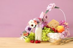Image of fruits and cheese in decorative basket with flowers over wooden table. Symbols of jewish holiday - Shavuot. Image of fruits and cheese in decorative Royalty Free Stock Photos