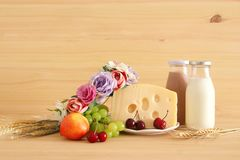 Image of fruits and cheese in decorative basket with flowers over wooden table. Symbols of jewish holiday - Shavuot. Image of fruits and cheese in decorative Stock Photos