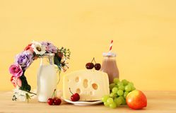 Image of fruits and cheese in decorative basket with flowers over wooden table. Symbols of jewish holiday - Shavuot. Image of fruits and cheese in decorative Stock Photography