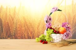 Image of fruits and cheese in decorative basket with flowers over wooden table. Symbols of jewish holiday - Shavuot. Image of fruits and cheese in decorative Royalty Free Stock Image