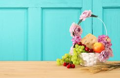 Image of fruits and cheese in decorative basket with flowers over wooden table. Symbols of jewish holiday - Shavuot. Image of fruits and cheese in decorative Stock Image