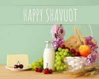Image of fruits and cheese in decorative basket with flowers over wooden table. Symbols of jewish holiday - Shavuot. Image of fruits and cheese in decorative Royalty Free Stock Images