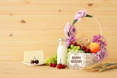 Image of fruits and cheese in decorative basket with flowers over wooden table. Symbols of jewish holiday - Shavuot. Image of fruits and cheese in decorative Royalty Free Stock Photography