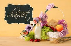 Image of fruits and cheese in decorative basket with flowers over wooden table. Symbols of jewish holiday - Shavuot. Royalty Free Stock Images