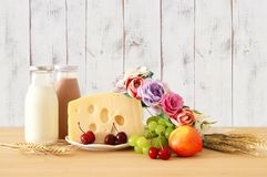 Image of fruits and cheese in decorative basket with flowers over wooden table. Symbols of jewish holiday - Shavuot. Image of fruits and cheese in decorative Royalty Free Stock Photo