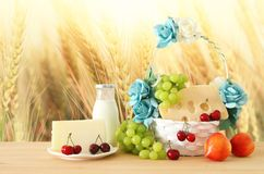 Image of fruits and cheese in decorative basket with flowers over wooden table. Symbols of jewish holiday - Shavuot. Stock Photos